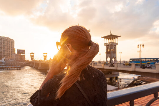 Female tourist with red hair making smartphone call near Stanley bridge at sunset, rear view, Alexandria, Egypt