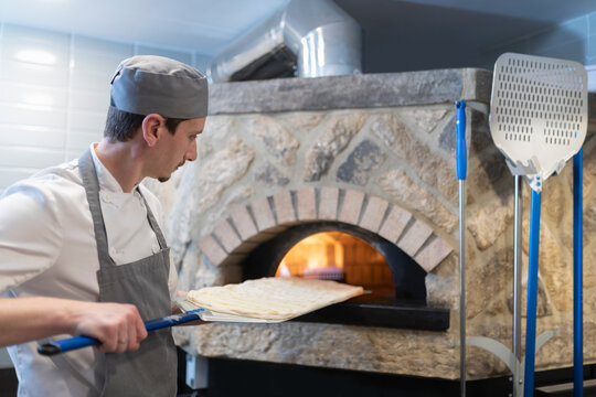 Chef putting dough of Pinsa Romana, a Roman style pizza blend reducing sugar and saturated fat, containing rice and soy with less gluten, into the oven