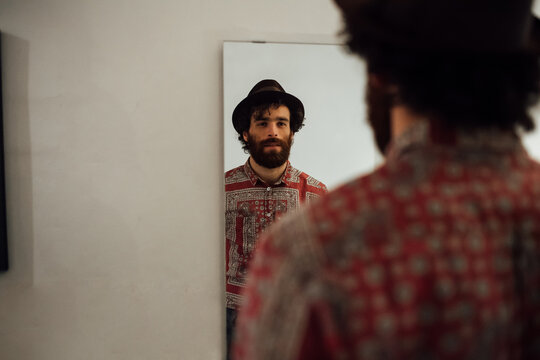 Bearded young man looking into mirror at home