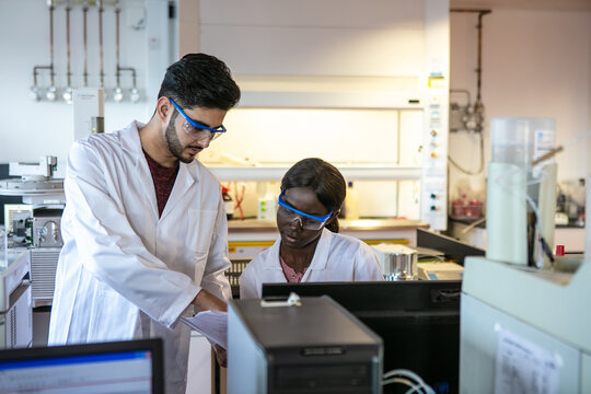 Young male and female scientists looking at results in laboratory, cropped