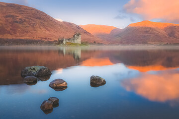 Scottish Highlands landscape of the historic ruins of Kilchurn Castle reflected on a calm, peaceful Loch Awe with sunset or sunrise golden light.