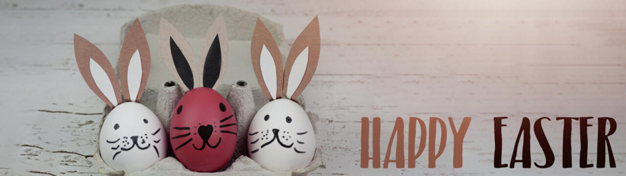 Happy Easter background banner panorama greeting card -Close-up from white and pink cute funny painted eggs and easter bunny in egg carton on rustic white vintage shabby wooden table
