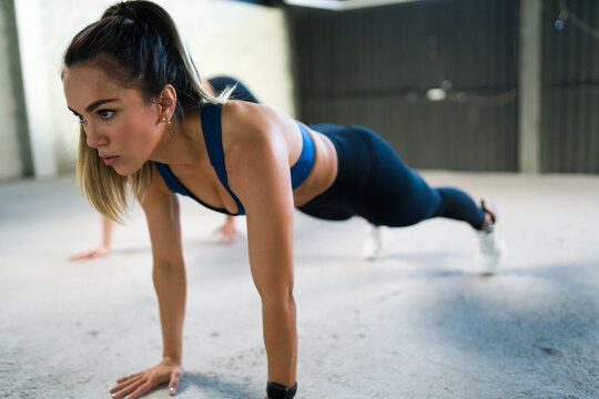 Side view of a beautiful latin woman doing a plank