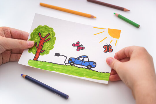 Young boy holding a childlike drawing of an electric car going for a drive outdoors in his hands
