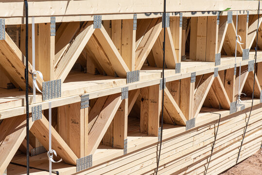 Prefab floor trusses stacked at a new home construction site, horizontal