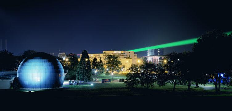WOLFSBURG, GERMANY - Oct 12, 2020: Planetarium in Wolfsburg at night with laser beam through the City from Phaeno