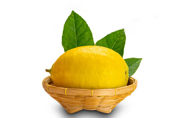 Fototapete - Ripe lemon with leaves in a bammboo basket on white background with clipping path.