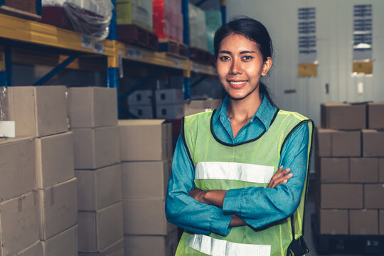 Portrait of young woman warehouse worker smiling in the storehouse . Logistics , supply chain and warehouse business concept .