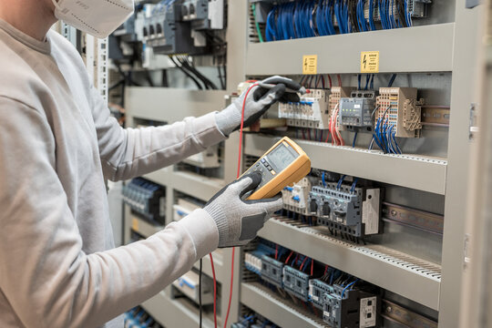 Electricians hands testing current electric in control panel