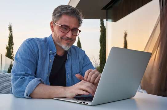 Bearded man working online with laptop computer at home on terrace. Home office, browsing internet, tele working, video chat. Portrait of mature age, middle age, mid adult man.
