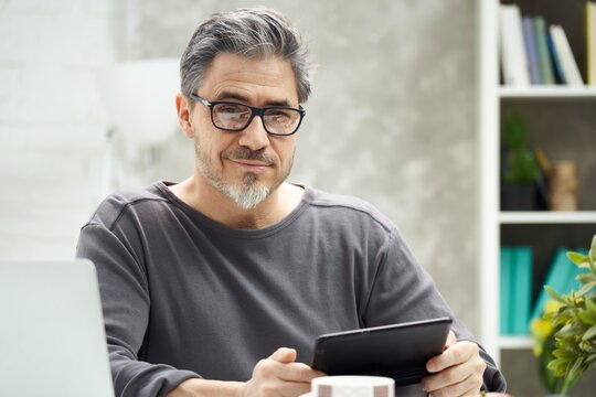 Bearded man working online with laptop computer at home sitting at desk. Home office, browsing internet, study room. Portrait of mature age, middle age, mid adult man in 50s.
