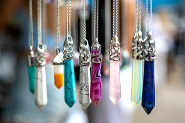 Multi colored gemstones and crystal pendants blurred background
