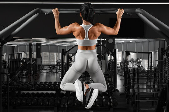 Athletic girl doing pull up exercise on horizontal bar. Fitness woman working out in gym