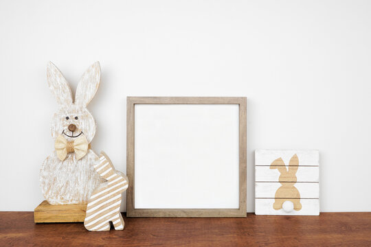 Mock up wood frame with Easter decor on a wood shelf. Shabby chic wood bunnies and sign. Square frame against a white wall. Copy space.