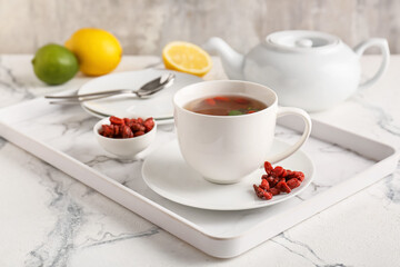 Cup with goji tea on light background