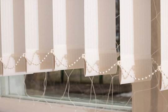 White fabric blinds on the window closeup