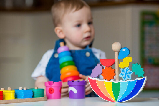 Balancing toys. A little boy is playing educational games. Children's wooden toy in the form of an umbrella, a colored pyramid and logic toys for children. Montessori Games for child development.
