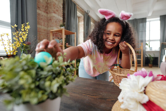 Happy little girl with toothy smile putting painted Easter egg into flowerpot
