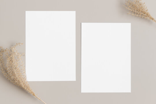 Two white invitation cards mockup with a dried grass decoration on a beige table. 5x7 ratio, similar to A6, A5.