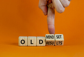 Old mindset and results symbol. Businessman turns wooden cubes and changes words 'old mindset' to 'old results'. Beautiful orange background. Business, old mindset and results concept. Copy space.