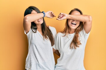 Hispanic family of mother and daughter wearing casual white tshirt smiling cheerful playing peek a boo with hands showing face. surprised and exited Wall mural