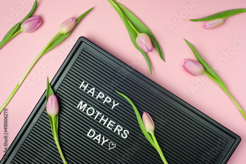 Happy Mother's day - text on black letter board on pink background with tulips. Pastel colors, soft image. Floral Greeting card.  Flat lay