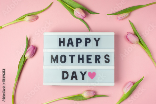Happy Mother's day - text on display lightbox on pink background with tulips. Pastel colors, soft image. Floral Greeting card.  Flat lay