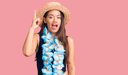 Young beautiful latin girl wearing hawaiian lei and summer hat pointing finger up with successful idea. exited and happy. number one. Wall mural