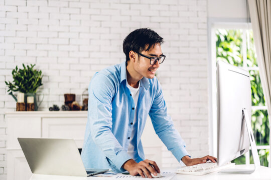 Handsome asian businessman looking at technology of laptop computer monitor while sitting on sofa.Young creative coworkers business people working and typing on keyboard at home