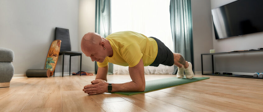 Time for fitness. Athletic mature man in sportswear standing in a plank on yoga mat while exercising at home in living room