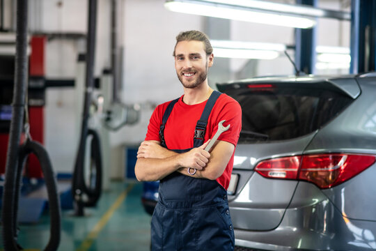Smiling man with wrench in auto repair shop