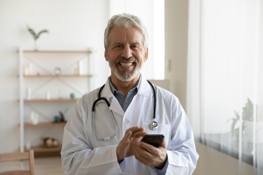 Portrait of smiling middle-aged Caucasian male doctor in white medical uniform use modern smartphone in clinic. Happy mature man GP or therapist look at camera consult patient on cellphone online.
