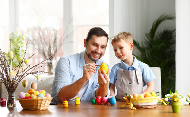 Delighted family: father and son painting Easter eggs together