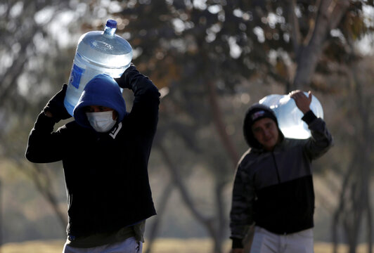 Migrants who traveled to northern Mexico seeking asylum in the United States, carry jugs of purified water at a migrant encampment in Matamoros