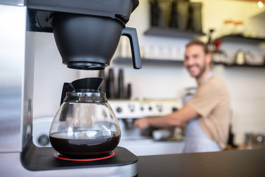Coffee maker with glass jug of coffee on counter