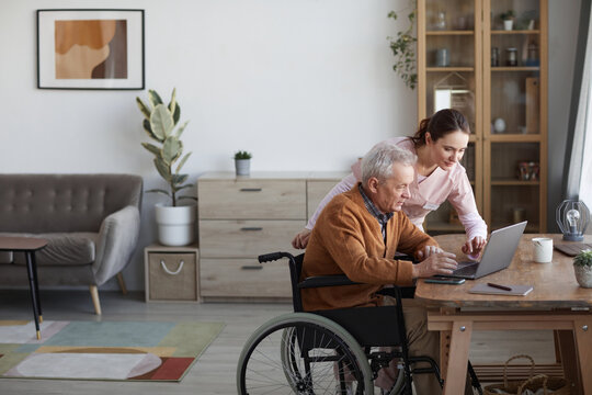 Side view portrait of senior man in wheelchair using laptop at retirement home with nurse assisting him, copy space