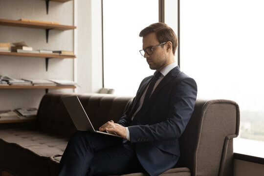 Close up confident businessman wearing glasses and suit using laptop, sitting on couch in modern office, focused entrepreneur working on online project, writing business email, browsing apps