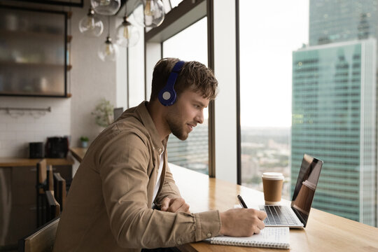 Side view motivated man wearing headphones writing, taking notes, using laptop, student looking at screen, watching webinar, listening to lecture, involved in online lesson, studying at home