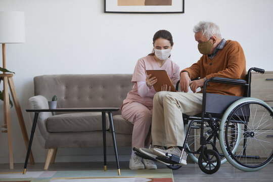 Full length portrait of young female nurse assisting senior man in wheelchair using digital tablet at retirement home, both wearing masks, copy space