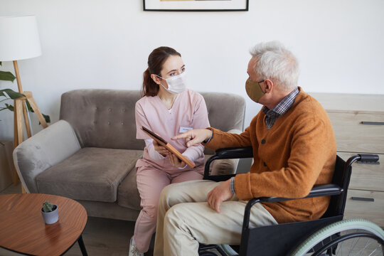 High angle portrait of young female nurse assisting senior man in wheelchair using digital tablet at retirement home, both wearing masks, copy space