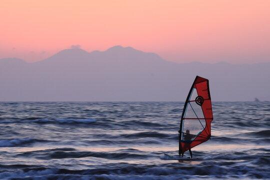 ウィンドサーフィンと夕暮れにかすむ山のシルエット