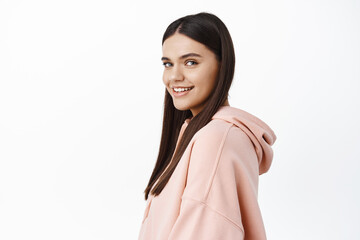 Young smiling and confident woman turn head at camera, standing in profile in hoodie, white...