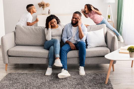 Black children fighting over their shocked parents