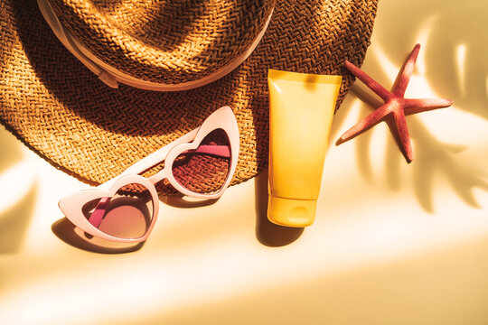 Travel summer accessories and sunscreen with shadow of tropical leaves on color background with copy space, Vacation planning concept