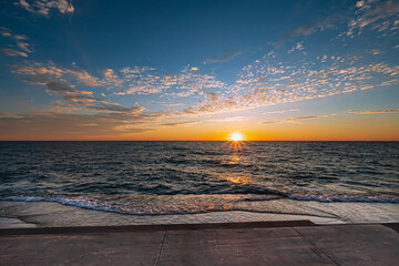 Beautiful early morning view of sunrise over the horizon on Lake Michigan. Sun is reflected on the lake water.