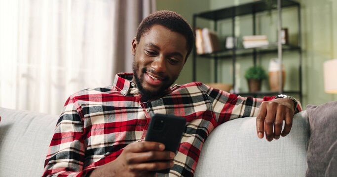 Close up of joyful young African American handsome man holding smartphone typing browsing online using social media mobile app sitting on sofa in living room. Happy male using cellphone at home