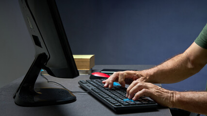 Fototapeta man hands using his computer keyboard, in the background books and mouse