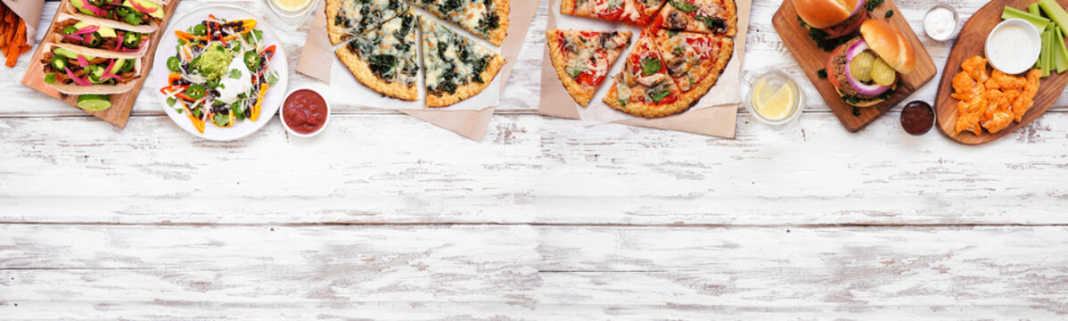 Healthy plant based fast food top border. Above view over a white wood banner background. Table scene with cauliflower crust pizzas, bean burgers, mushroom tacos and vegetarian sides. Copy space.
