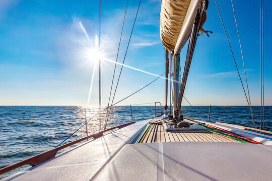 Sailing boat at calm open sea on a bright sunny day