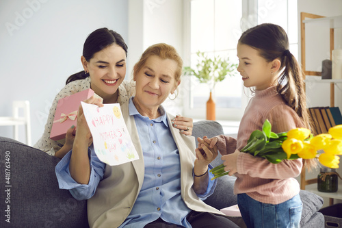 Grandmother holding a card made for her by her adult daughter and little granddaughter. Family congratulated her grandmother on Mother's Day by giving her a tulips, gift and handmade postcard.